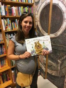 Lyndsey Pheloung-Beck holding a copy of children's picture book Can a Quokka Quack